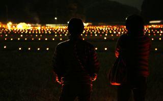 お年寄りたちと一緒に棚田に竹燈篭を並べる